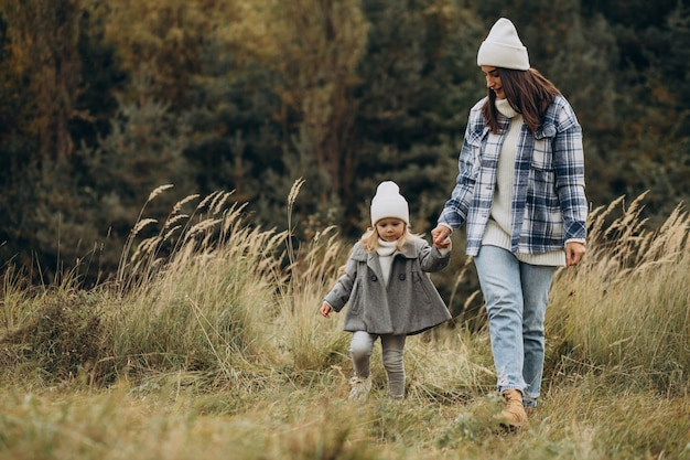 Mère avec petite fille ensemble par temps d'automne s'amusant