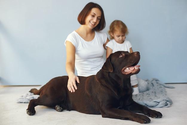 Mère et petite fille jouant avec un chien à la maison