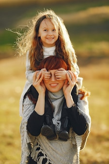 Mère avec petite fille jouant dans un champ d'automne
