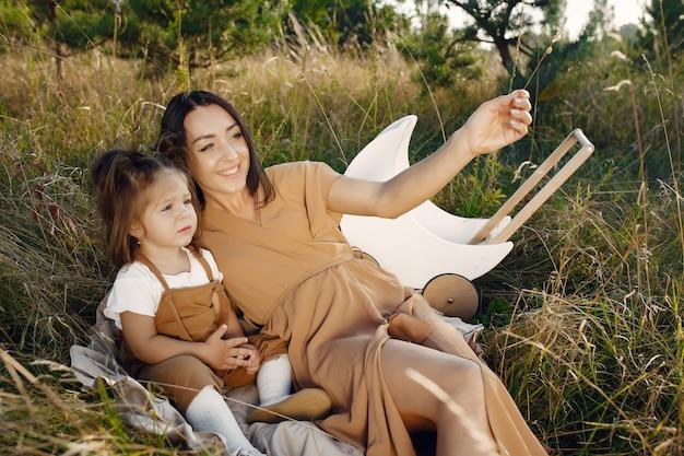 Mère avec petite fille jouant dans un champ d'été