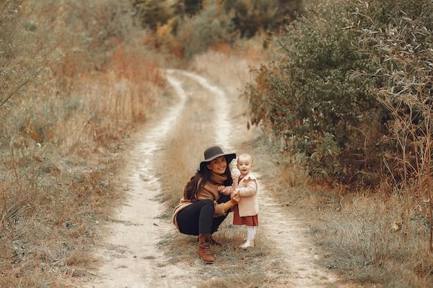 Mère avec petite fille jouant dans un champ