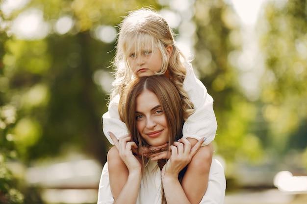 Mère avec petite fille jouant dans un parc d'été