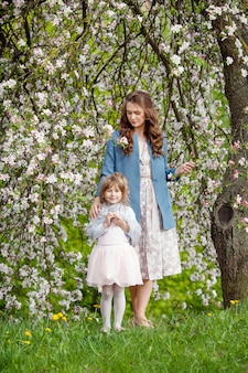 Mère et petite fille marchant dans le jardin de pommes en fleurs. maman aime son enfant. histoire du printemps. héhé dans la belle journée de printemps