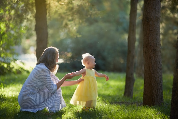 Mère et petite fille marchent dans la forêt d'été ensoleillée.