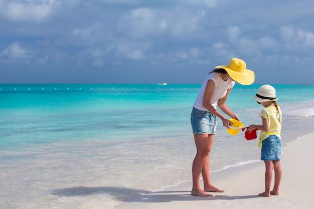 Mère et petite fille sur la plage pendant leurs vacances dans les caraïbes