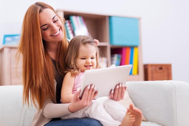 Mère avec petite fille profitant du net gratuit à la maison