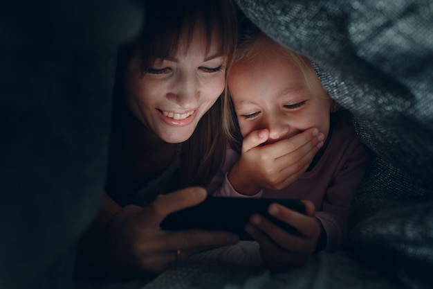 Mère avec une petite fille regardant le contenu sur smartphone dans le noir sous les couvertures.