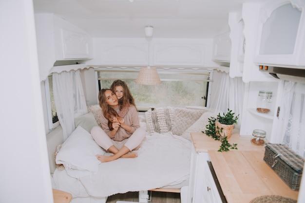 Mère et petite fille se détendre et s'amuser dans la campagne à l'intérieur du camping-car