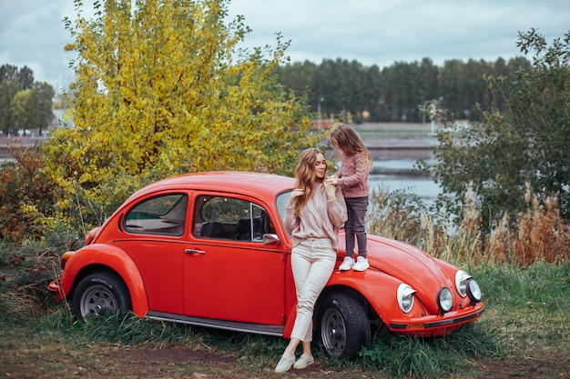 Mère et petite fille se détendre et s'amuser dans la campagne en vacances camping car avec voiture rétro rouge