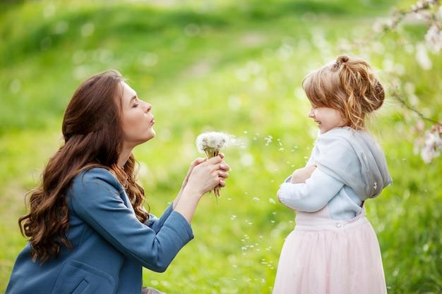 Mère avec petite fille soufflant au pissenlit - scène de plein air de style de vie dans le parc. concept de famille heureuse