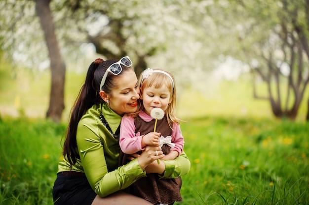 Mère avec la petite fille souffle sur un pissenlit