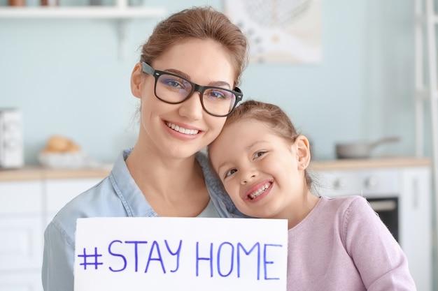 Mère avec petite fille tenant du papier avec texte rester à la maison à la maison