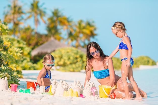 Mère et petites filles faisant château de sable sur la plage tropicale