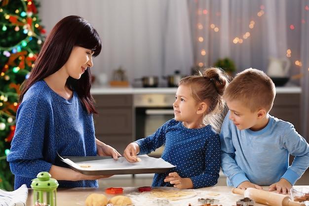 Mère et petits enfants faisant des biscuits de noël dans la cuisine