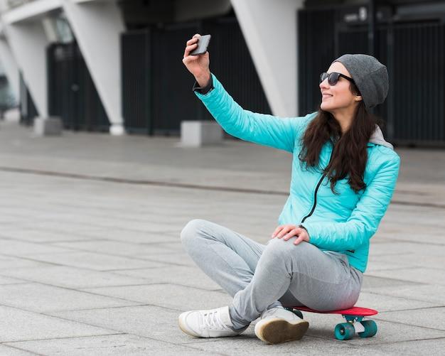 Mère sur planche à roulettes prenant selfie