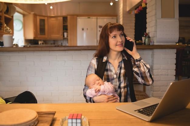Mère portant bébé tout en parlant au téléphone mobile