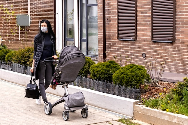 Une mère portant un masque de protection marche dans la rue avec un bébé dans une poussette