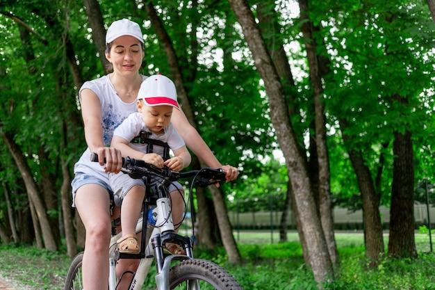 Mère porte un enfant dans une chaise d'enfant sur un vélo dans le parc en été