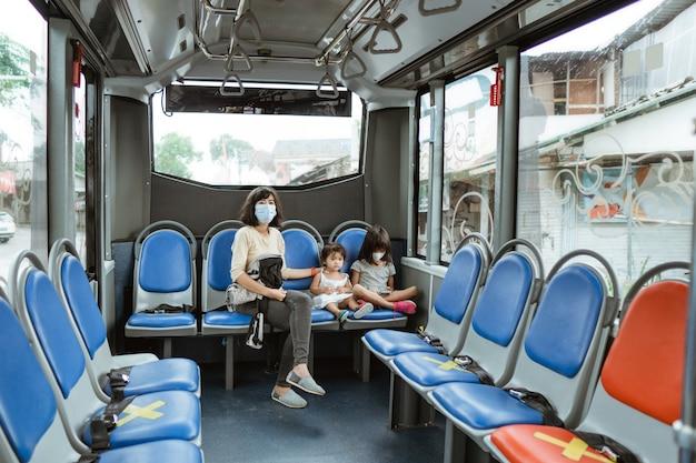 Une mère porte un masque et les deux petites filles s'assoient sur un banc dans le bus pendant le voyage