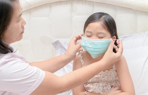Mère porter une fille masque de protection pour se protéger contre le virus de la grippe dans la chambre à coucher, les soins de santé et