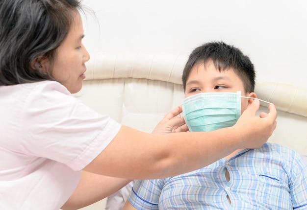 Mère porter des fils de protection masque pour protéger contre le virus de la grippe dans la chambre, les soins de santé et les malades