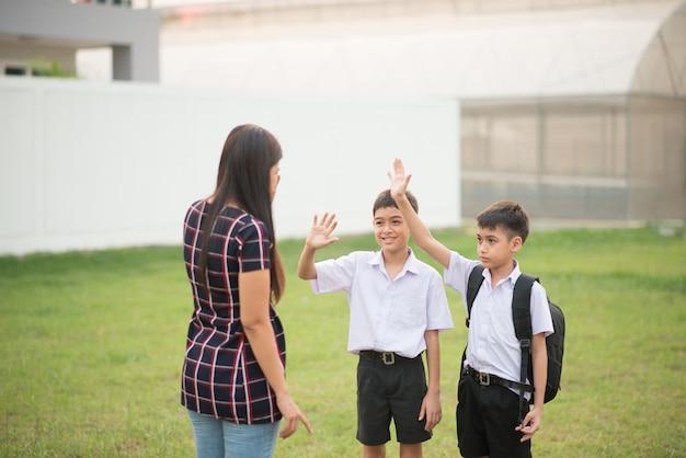 Mère prenant des fils à l'école ensemble, main levée dire au revoir