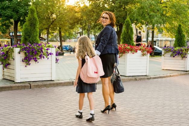 Mère prenant sa fille à l'école - vue arrière.
