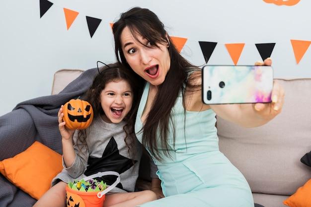 Mère prenant un selfie avec sa fille à l'halloween