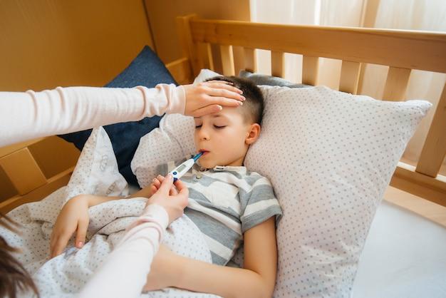 Une mère prend soin de son enfant qui a de la fièvre et de la fièvre. maladie et soins de santé