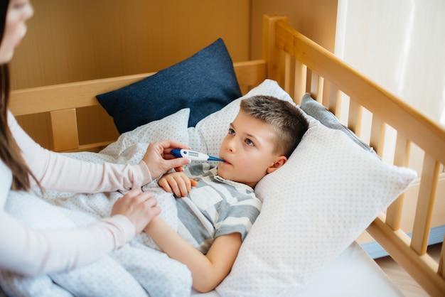 Une mère prend soin de son enfant qui a de la fièvre et de la fièvre. maladie et soins de santé.