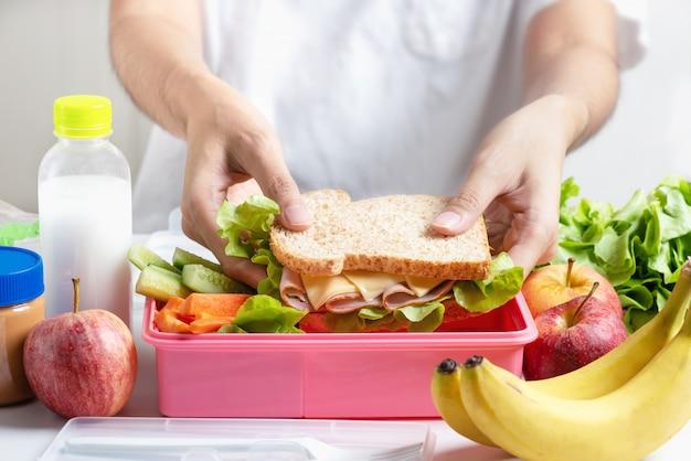 Mère préparant le coffret repas scolaire