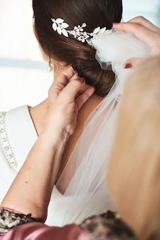Mère prépare sa fille pour un jour de mariage.