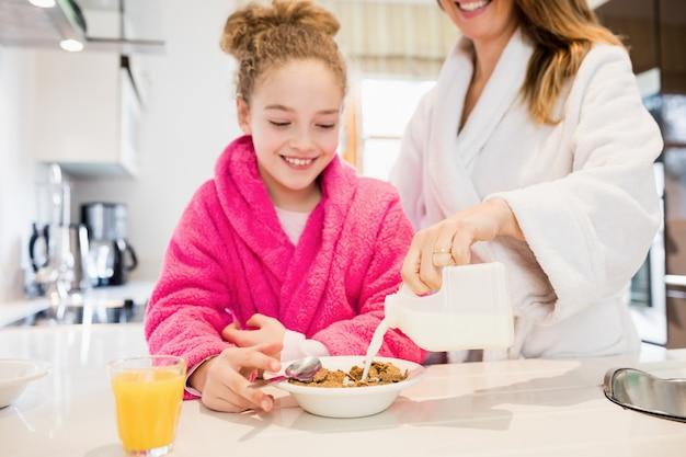 Mère préparer le petit déjeuner pour sa fille dans la cuisine