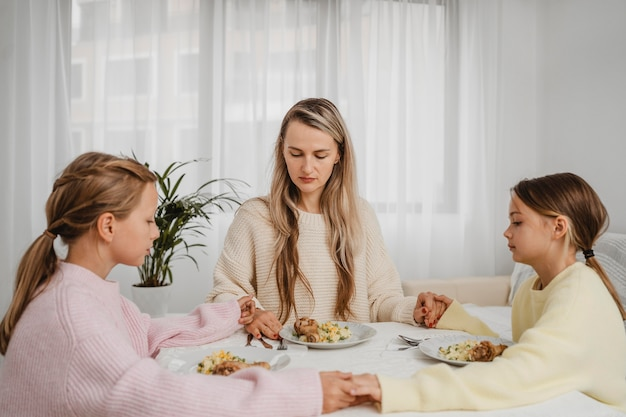 Mère priant avec les enfants à table