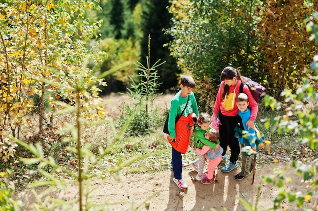 Mère de quatre enfants dans les montagnes. voyages en famille et randonnées avec enfants. les sœurs s'embrassent.