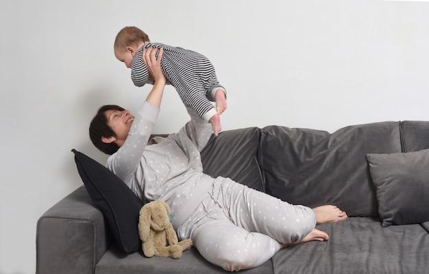 Une mère qui soulève son bébé sur le canapé à la maison