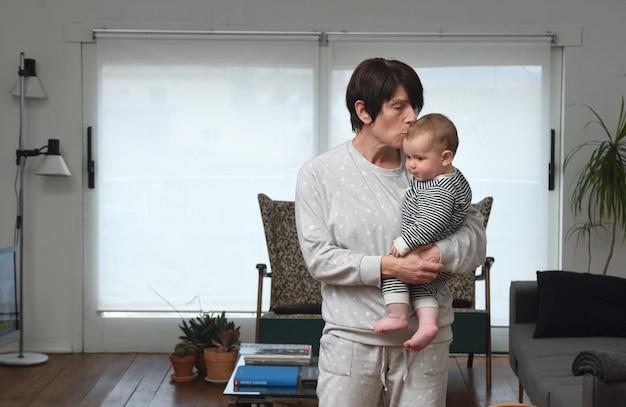 La mère qui tient le bébé et lui donne un baiser