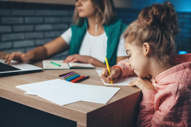 Mère de race blanche et travaille sur un ordinateur portable avec des affaires pendant que sa fille dessine avec des crayons colorés