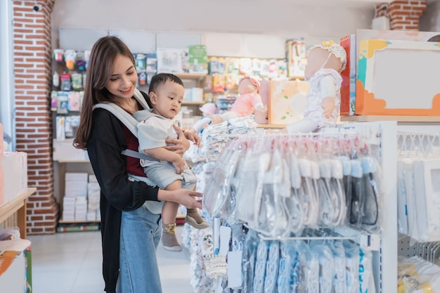 Mère ramasser un produit au magasin pour bébés tout en portant son fils