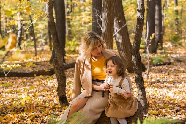 Mère réconfortant sa petite fille qui pleure dans les émotions de la nature d'automne et le concept de famille
