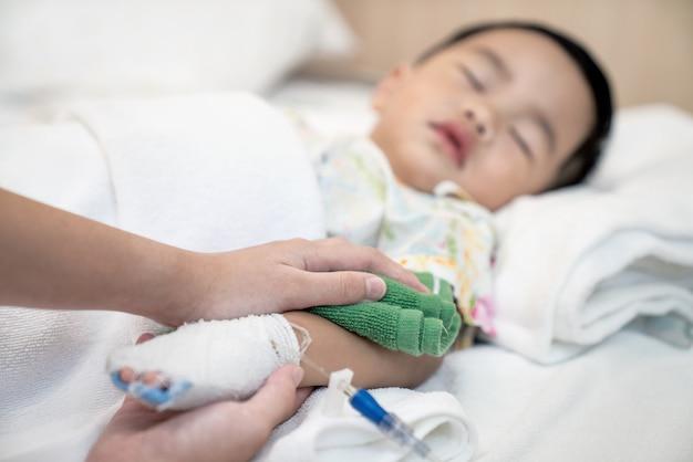 Mère refroidit la température de son enfant par l'eau dans l'hospotal