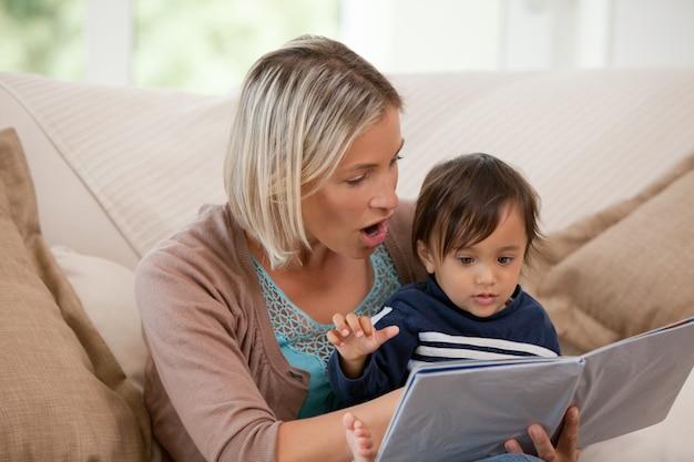 Mère regardant un livre avec son fils