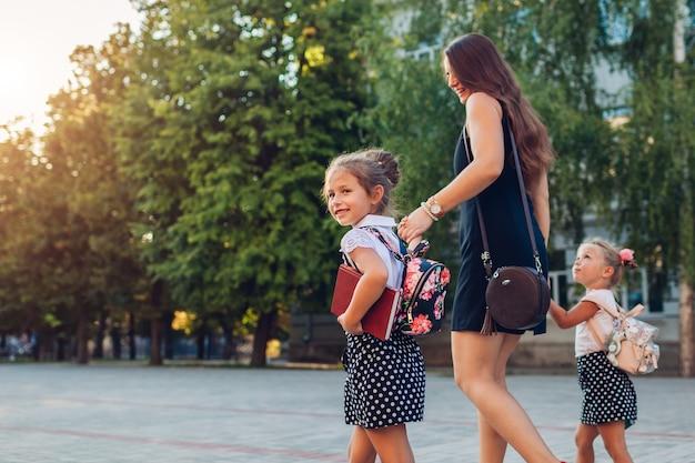 Mère rencontrant des enfants filles après les cours à l'extérieur de l'école primaire la famille rentre à la maison avec des livres. retour à l'école. éducation