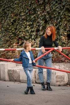 Une mère rousse élégante et sa fille parlent chaleureusement. enfant heureux et sa maman dans la rue. mère célibataire réussie avec sa fille pour une promenade. relation familiale chaleureuse