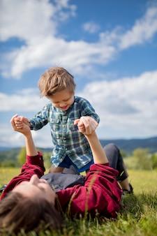 Mère s'amuser avec un fils sur une prairie en montagne