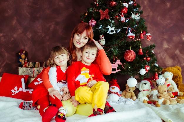 Mère s'assoit avec ses enfants devant un arbre de noël