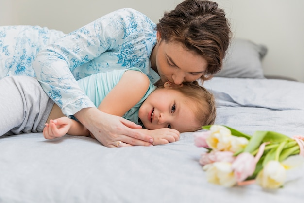 Mère s'embrasser à sa fille innocente sur le lit