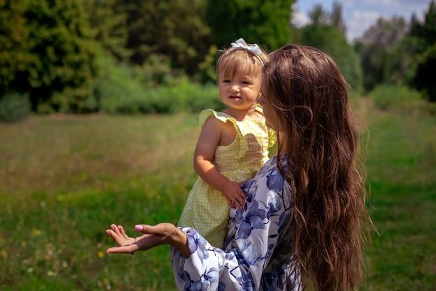 Mère avec sa belle petite fille sur ses mains parle et pointe de côté dans le parc verdoyant