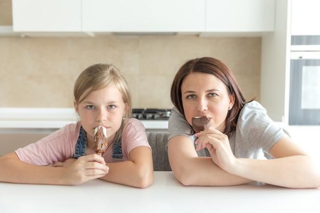 Mère avec sa fille de 12 ans assise dans la cuisine en train de manger de la glace, bonnes relations parents-enfant, moments heureux ensemble