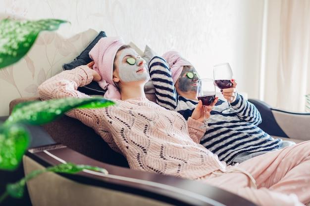 La mère et sa fille adulte ont appliqué des masques faciaux et des concombres sur les yeux. les femmes se détendre tout en ayant du vin